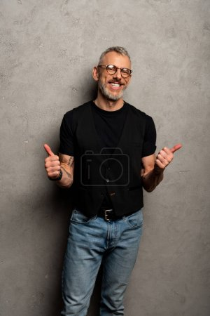 Photo for Cheerful man in glasses showing thumbs up on grey - Royalty Free Image
