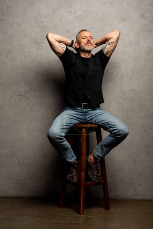handsome man with tattoos sitting on stool on grey