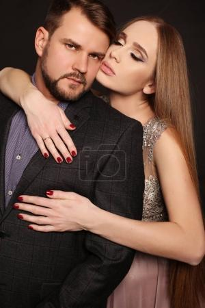Photo pour Fashion studio photo du beau couple en vêtements élégants. bel homme posant avec une femme enceinte magnifique - image libre de droit
