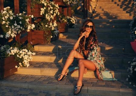 schöne Frau mit dunklen langen Haaren in Badeanzug und Sonnenbrille