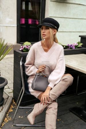 Photo pour Mode photo en plein air de magnifique femme sexy avec des cheveux blonds dans une tenue élégante, assis dans un café de la ville - image libre de droit