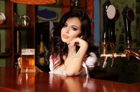 Photo pour Photo intérieure de la belle femme barman posant dans le comptoir du bar avec un verre de bière - image libre de droit
