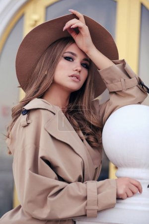 Photo for Fashion outdoor photo of beautiful girl with dark hair in elegant beige coat and hat posing in autumn street - Royalty Free Image
