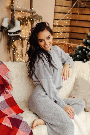 Photo pour Photo d'intérieur de mode d'une belle femme aux cheveux foncés en vêtements confortables célébrant Noël à la maison décorée - image libre de droit