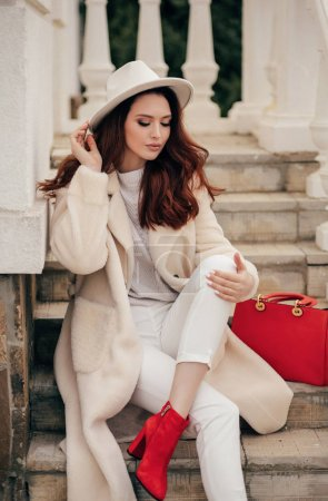 Photo for Fashion outdoor photo of beautiful sensual woman with dark hair in elegant beige coat and white hat posing in the street - Royalty Free Image