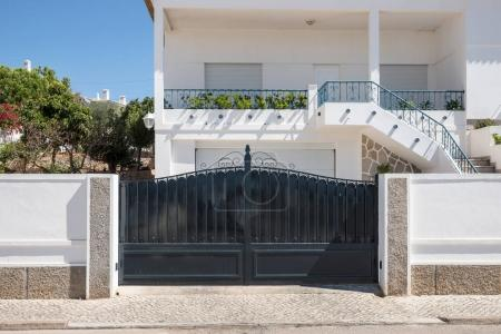 Photo for New dark metal double gates for entry of cars into the yard closed - Royalty Free Image