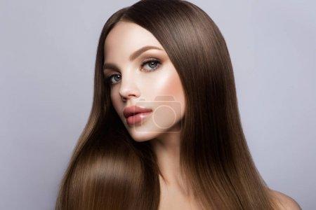 Photo pour Visage de femme beauté Portrait. Modèle belle fille avec les lèvres de couleur parfaite peau propre douce roses. Brune cheveux longs. Isolé sur fond beige - image libre de droit