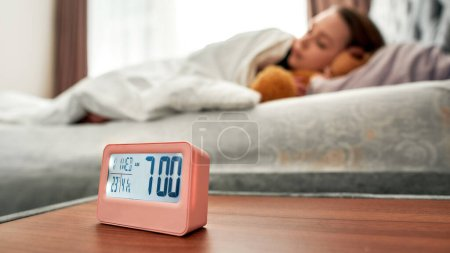 Photo for Asleep caucasian young woman in the background with digital alarm clock in focus. Selective focus. Horizontal shot - Royalty Free Image