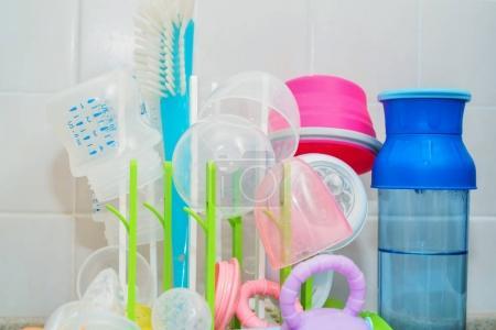 Photo pour Fermer les biberons colorés séchant sur un support en plastique blanc - image libre de droit