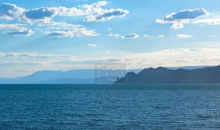 The sea with the silhouette of a jagged rocky shore in the distance with mountains in the background of the cloudy sky