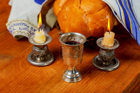 Sabbath image - Silver kiddush cup, crystal candlesticks with lit candles, and challah