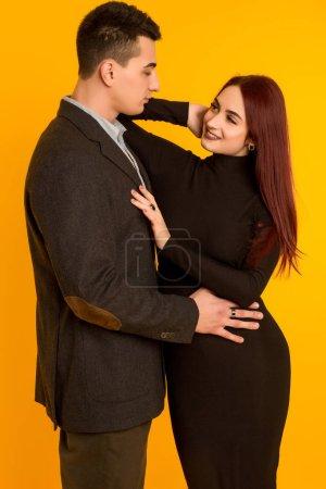 guy in a jacket hugs the girl in a black dress