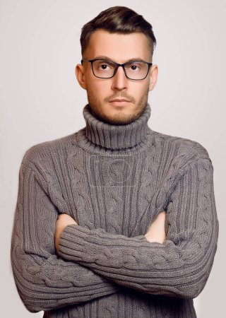 Beautiful fashionable guy with glasses and a sweater posing