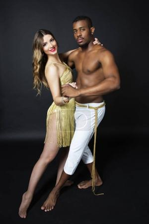 Fashion close up portrait of attractive dancing couple in sensual hugs. Holding hands. Dancing latino. Passion Love. The girls perfect skin facial make-up. The guys pumped abs. Gold toned colors