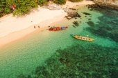 Drone flying under the amazing tropical bay with clear water, white beach and traditional longtail boats. Aerial view of beautiful bay and sea with clear turquoise water. Paradaise island, Thailand.
