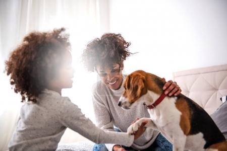 Foto de Joven madre afroamericana, pasar tiempo con su hija jugando con perro. - Imagen libre de derechos