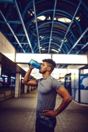 Photo pour Bel homme s'arrêtant pour une eau tout en faisant de l'exercice . - image libre de droit