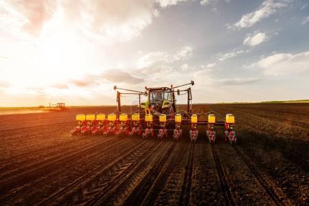 Photo pour Tracteur travaillant sur les terres agricoles au coucher du soleil . - image libre de droit