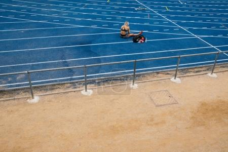 Photo for Rear view of an athletics woman sitting on the racetrack. - Royalty Free Image
