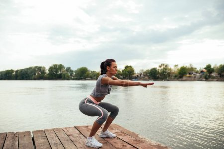 Photo for Portrait of an athlete woman doing squats outdoors by the lake. - Royalty Free Image