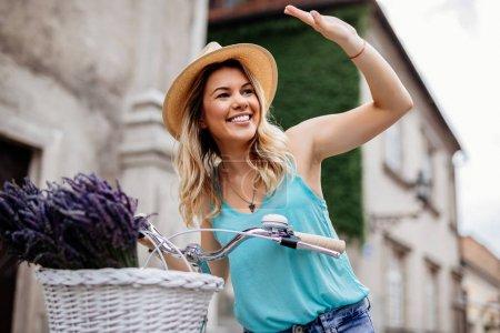 Photo pour Tourné d'une belle jeune femme agitant tout en poussant un vélo à l'extérieur . - image libre de droit