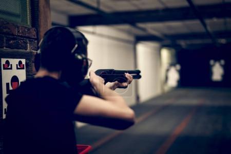 Photo pour Homme visé fusil de chasse à la cible dans le champ de tir intérieur ou champ de tir - image libre de droit