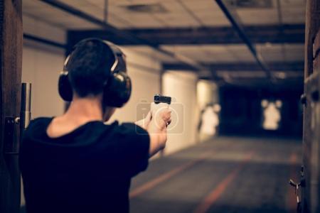 Man aiming shotgun at target in indoor firing rang...