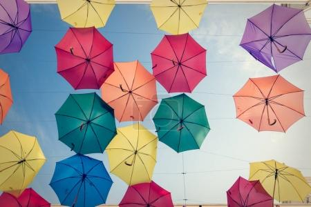 Umbrellas hung between houses