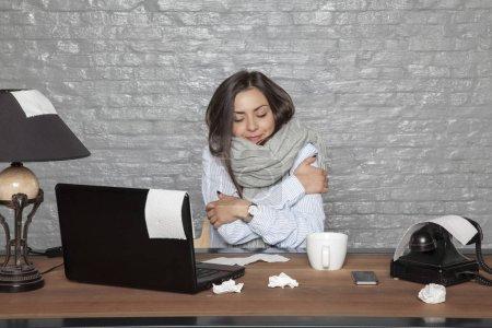 Photo pour Une femme d'affaires malade tremble de froid et de surmenage - image libre de droit