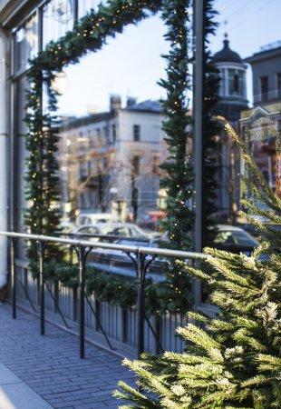 citylife on Christmas. Decoration of showcase outside street, gift card background. garland, tree