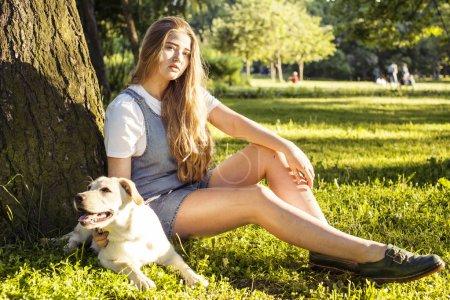 Foto de Atractiva rubia jovencita jugando con su perro en el parque verde en verano, el concepto de pueblo de estilo de vida, verdadera amistad - Imagen libre de derechos
