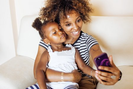 Afro-american mother with daughter taking selfie