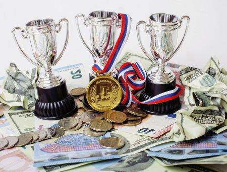 Photo pour Concept gagnant sportif : trois tasses entre différentes devises euro, dollar, rubl, médaille d'or première place close up - image libre de droit