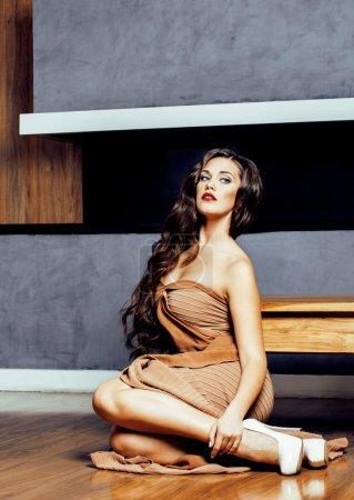 beauty yong brunette woman sitting near fireplace at home, winte