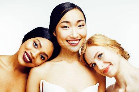Photo pour Trois femmes de différentes nations: asiatique, caucasien, afro-américain ensemble isolé sur fond blanc sourire heureux, gros plan type diversifié sur la peau, le concept de peuple lifestyle - image libre de droit