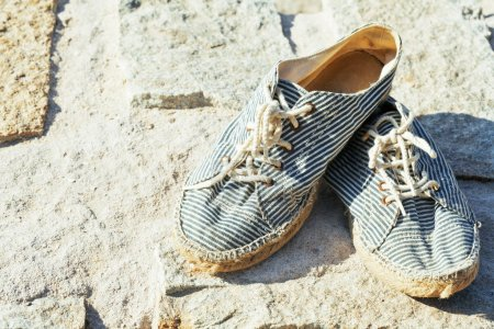 vintage old shabby sneakers at seacost