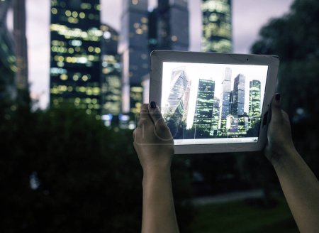 In the bottom left of the photo are hands holding tablet, whose screen contains color photo of Moscow-city business center, urban people concept