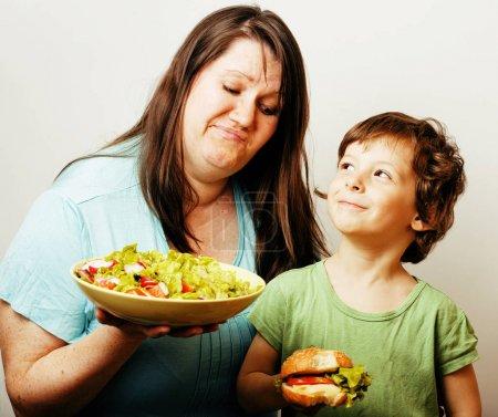 woman holding salad and boy with hamburger