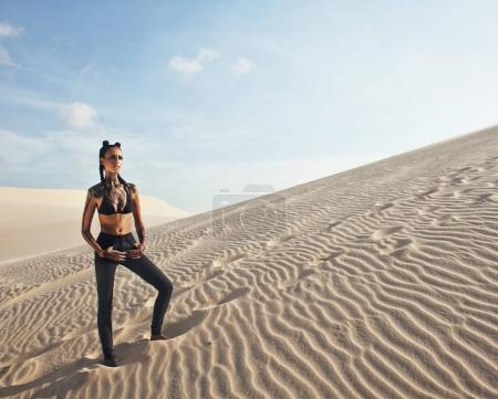 Young pretty woman in white sand dunes like a goddes of darkness