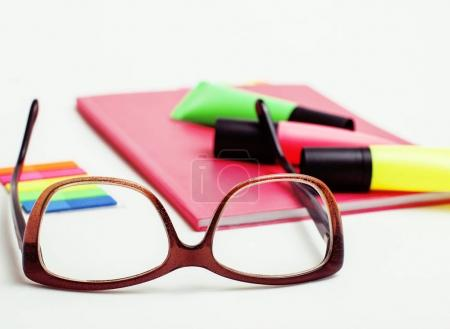 business, education and technology concept - close up of notebook, paper stickers, glasses, pencil different new stuff on white background