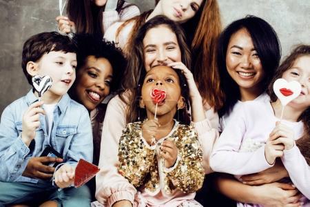 Photo pour Concept de mode de vie et les gens: jeunes jolies femmes de la diversité des nations avec les enfants d'âge différents célèbrent ensemble sur la partie jour de naissance heureux souriant, faisant selfie - image libre de droit