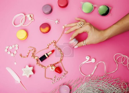 woman hands holding macaroons and jewellery