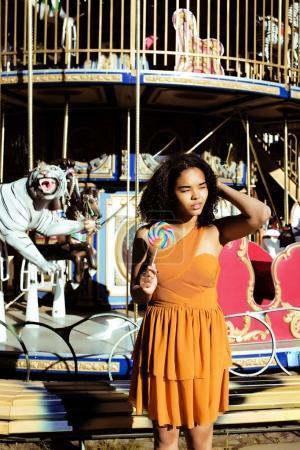 teenage girl with candy near carousels