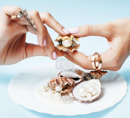 beautiful woman hands with pink manicure holding plate with pearls and sea shells, luxury jewelry concept