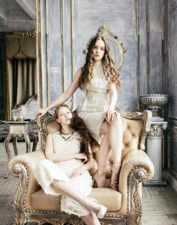 pretty twin sisters in luxury interior