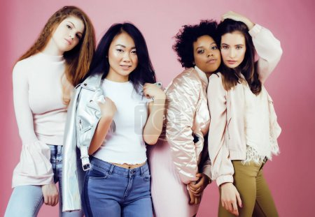different nation girls with diversity in skin, hair. Asian, scandinavian, african american cheerful emotional posing on pink background, woman day celebration, lifestyle people concept