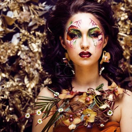 Photo pour Beauté femme avec visage art et bijoux de fleurs orchidées gros plan, maquillage créatif - image libre de droit