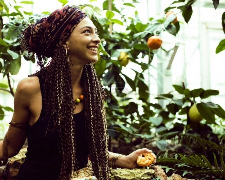Young cute smiling woman in park with oranges