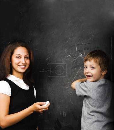 little cute boy in glasses with young real teacher, classroom studying at blackboard school