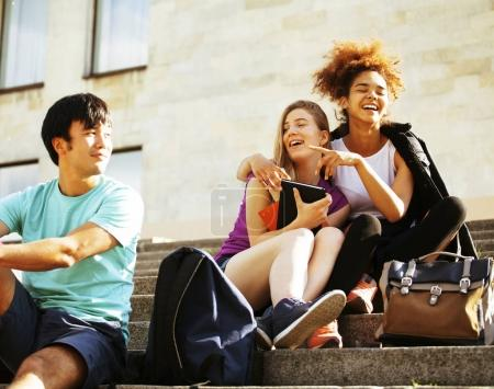 Photo for Cute group of teenages at the building of university with books huggings, smiling, back to school - Royalty Free Image
